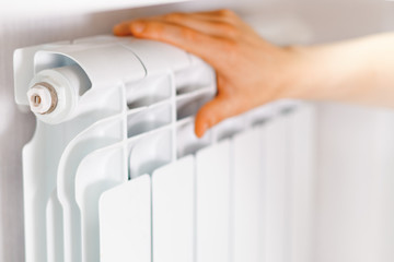 Arm put on  heating white radiator.