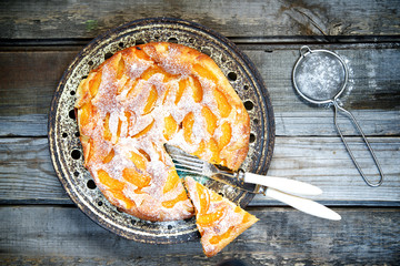 Cake with peaches, sprinkled with powdered sugar