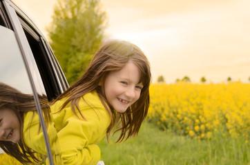 Hübsches lachendes Mädchen lehnt sich aus dem Autofenster