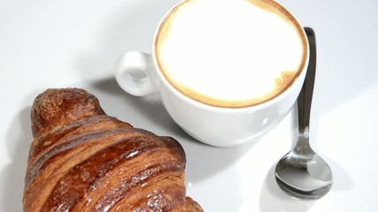 Croissant and cappuccino on a white plate rotating.