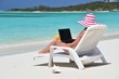 Girl with a laptop on the tropical beach. Exuma, Bahamas