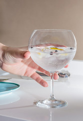 Hand picking gin tonic cocktail served on a glass