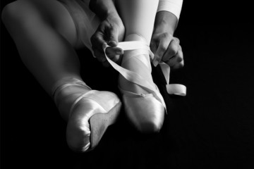 Ballerina sit down on floor to put on slippers prepare to perfor