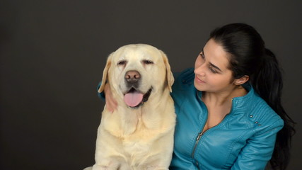 Young beautiful woman and labrador on a dark background