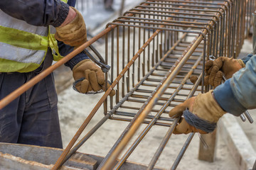 workers hands fixing steel reinforcement bars