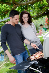 happy young loving couple cooking barbecue party wine