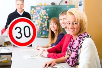 Fahrlehrer mit seiner Klasse mit Fahrschülern