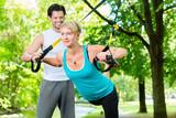 Fototapety Fitness - Leute beim Suspension training im Park