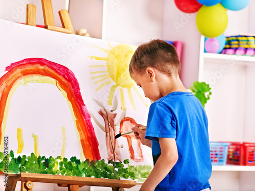 Child painting at easel.