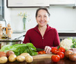 Happy mature woman with cutting tomato