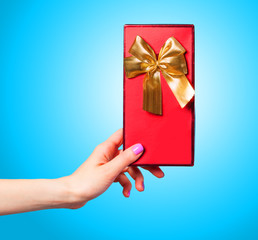 Hand holding red gift on blue background.