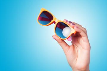 Hand holding sunglasses