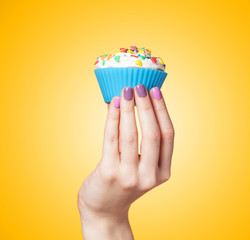 Hand holding cupcake on yellow background