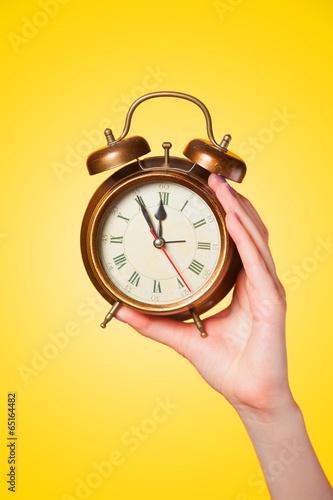 Hand holding alarm clock on yellow background. - 65164482