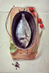 Fresh dorada fish in a stewing dish prepared for baking, with to