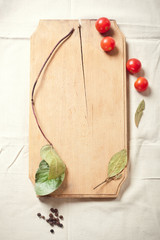 Cooking: tomatoes, spices and herbs for cooking, on wooden cutti
