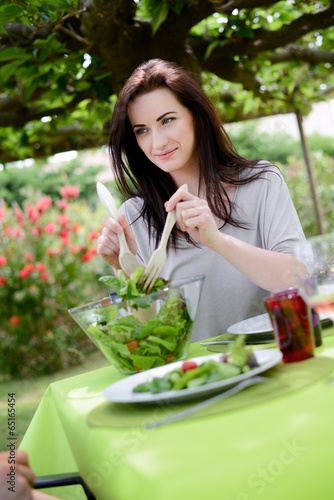 cheerful cute young woman eat salad at barbecue party  - 65165454