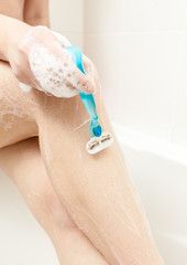photo of woman shaving leg at bath