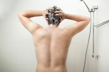 Photo of from back of muscular man washing head