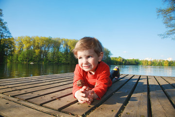 Portrait of a smiling boy laying on a dock at a sunny lake