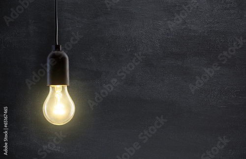 canvas print picture Light bulb lamp on blackboard background with copy space