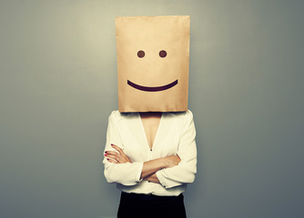 woman hiding under smiley paper bag