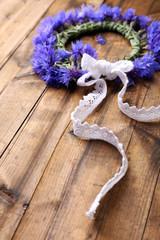 Fresh cornflower wreath on wooden background