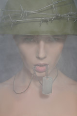 Portrait of woman in army helmet with a coin