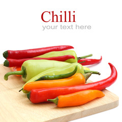 Red & green chillies peppers on chopping board