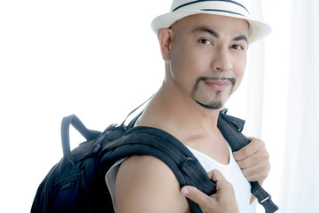 smart Asian man travel with black baggage and white hat