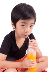 Portrait of happy little boy drinking orange juice. Isolated ove