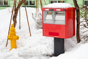 A traditional red japanese postbox at winter time covered in sno