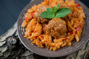 Braised cabbage and meatballs decorated with mint leaves