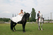 bride and groom sitting on a horse