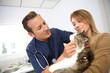 Veterinarian examining cat in clinic