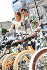 Couple choosing bikes in rental shop