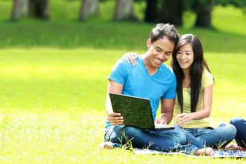 happy young couple using laptop outdoor