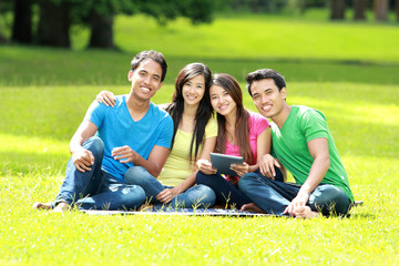 Group of young student using tablet pc outdoor
