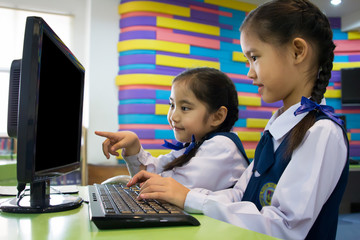 Little cute Asian girl using computer