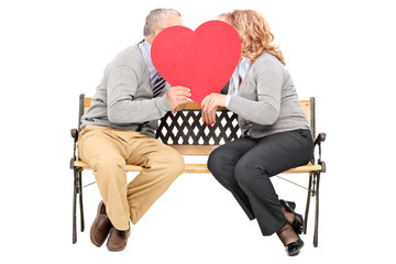 Elderly couple chatting behind a big red heart