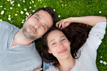 Attractive couple lying in grass at the park