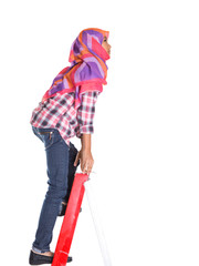 Young Asian Muslim school girl climbing a ladder with backpack