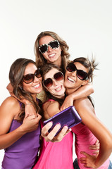portrait of four friends, taking photos with a smartphone