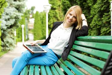 Smiling woman sitting on the bench with tablet computer