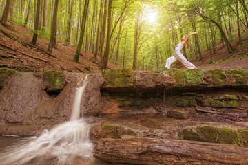 Relaxation, Woman practices yoga at the waterfall