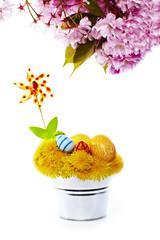 Oster Blumennest im Eimer mit Windrad und Kirschblüten