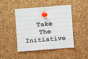 The phrase Take The Initiative on a cork notice board