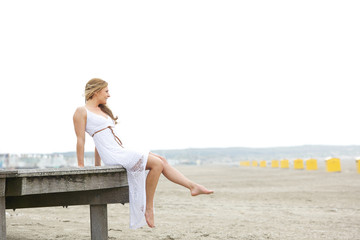 Young woman sitting alone at the beach