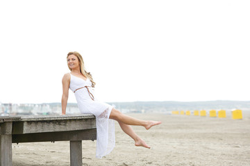 Young woman in white dress sitting at the beach