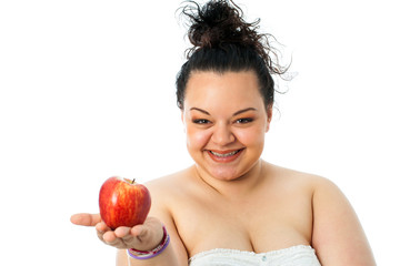 Young obese girl holding red apple.